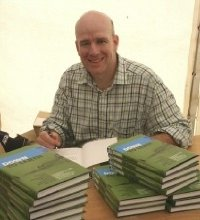 "Owen Zupp signing copies of his book ""Down To Earth"" (Image from Owen's website)"